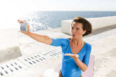 Portrait of beautiful woman with dark short hair in blue swimsuit sitting on yoga mat and looking in her mobile phone while sending air kiss with sea on background
