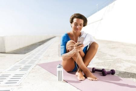 Portrait of beautiful smiling woman with brown short hair in blue swimsuit and earphones sitting on purple yoga mat and using her cellphone isolated