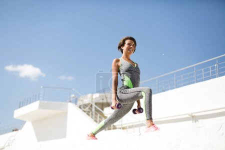 Portrait of beautiful smiling woman in modern gray sport suit and pink sneakers doing exercise with dumbbells while happily looking straight