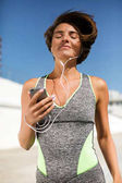 Portrait of beautiful smiling woman with brown short hair in modern gray sport suit holding cellphone with earphones and dreamily closing her eyes while jogging isolated