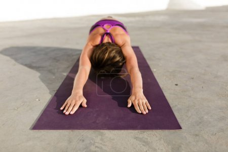 Portrait of woman sitting and pulling her hands while training yoga poses on purple yoga mat. Pretty lady with dark short hair in sporty top practicing yoga isolated