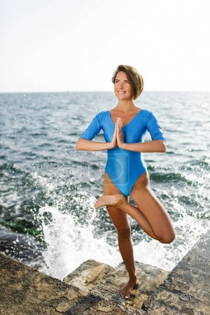 Portrait of smiling woman standing meditating and training yoga poses while happily looking aside by the sea. Beautiful lady in swimsuit practicing yoga with amazing sea view on background