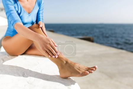 Close up photo of woman body sitting on white stone with beautiful sea view on background