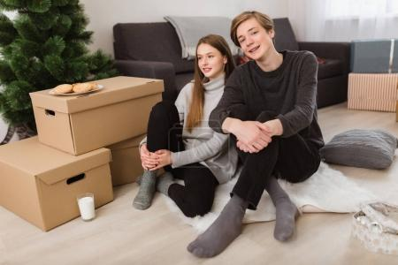 Portrait of beautiful girl and boy sitting on floor at home and happily looking in camera