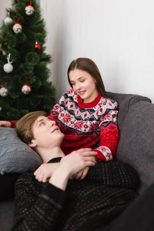 Portrait of smiling young couple lying on sofa at home and spending time together while dreamily looking on each other