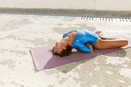 Close up photo of young woman with dark sort hair lying on yoga mat and training different yoga poses while closing her eyes. Beautiful lady in blue swimsuit meditating and practicing yoga isolated