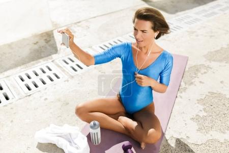Portrait of nice woman with dark short hair in blue swimsuit sitting on yoga mat and amazedly looking in her cellphone while taking photo on frontal camera isolated