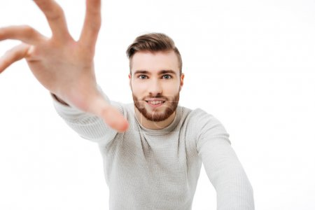 Handsome guy reaching out to the camera isolated. Young man trying to take your camera over white background