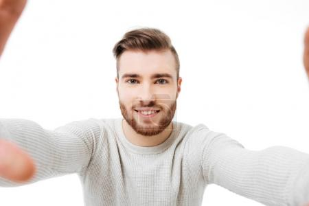 Young attractive man taking selfie over white background. Front camera view
