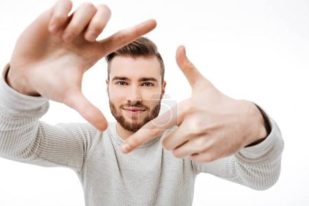 Young man making finger frame as a director of photography and smilibg over white background isolated