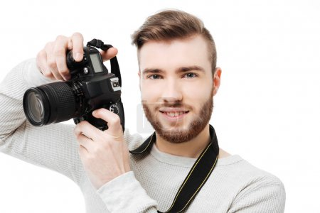 Close up portrait of handsome young man taking photos with DSLR camera isolated