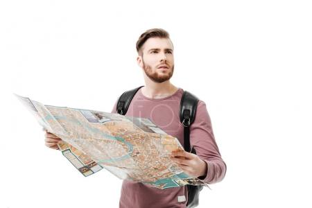 Portrait of young man thoughtfully looking aside with open map in hands and backpack on white background. Thoughtful boy standing with road map isolated