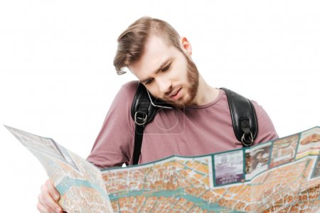 Portrait of young man talking on his mobile phone while holding open map in hands on white background. Cool boy standing with road map and black backpack isolated