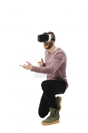 Portrait of cool boy in virtual reality glasses playing in shooter game on white background. Young man using visual reality glasses isolated
