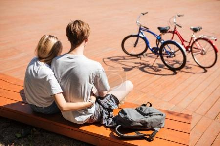 Close up photo of cute couple from back sitting on bench and embracing with backpack beside. Portrait of young man and lady spending time together with red and blue bicycles nearby
