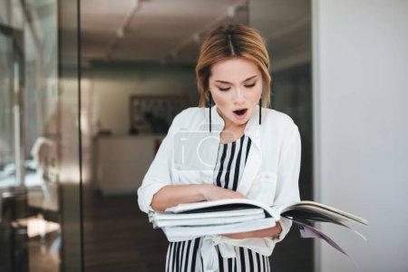 Portrait de jeune fille aux cheveux blonds, maintenir les livres en mains et amazedly à la recherche à ce sujet. Choqué de fille en robe dénudée et chemise blanche debout près de la porte des revues en mains