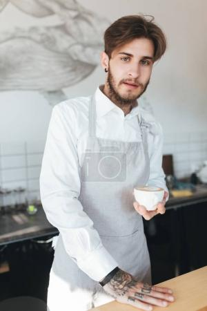 Portrait of young barista looking in camera with cup of coffee in hand in restaurant. Man in apron and white shirt standing with cup of coffee at his workplace in coffee shop