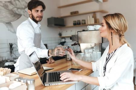 Młody barista w fartuch i białej koszuli, dając szklankę wody do ładnej dziewczyny. Piękna Pani, blond włosy, siedząc przy kasie i pracę na swojego laptopa w kawiarni