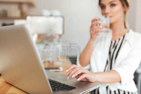 Pretty girl with blond hair drinking water in restaurant. Beautiful girl in white shirt working on her laptop in coffee shop. Close up lady hand typing on computer at cafe