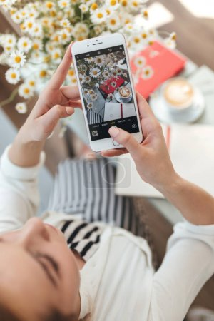 Beautiful girl with blond hair sitting in coffee shop and making photos. Young girl taking pictures of flowers,cup of coffee and books on table in restaurant. Close up woman hands holding cellphone