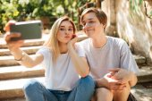 Portrait of young couple sitting on stairs in park and making cute selfie together. Smiling boy and beautiful girl with blond hair looking in camera while taking photos on mobile phone frontal camera