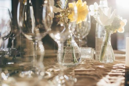 Photo pour Verres à vin au coucher du soleil. Banquet de mariage. Table d'hôtes, décorée de bougies et de fleurs, servie avec couverts et vaisselle et recouverte d'une nappe. Table décorée pour la réception de mariage - image libre de droit
