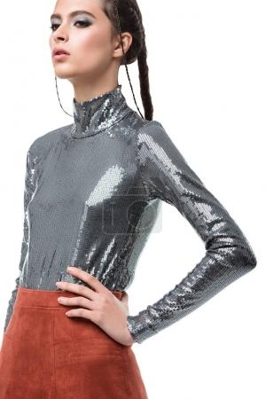Portrait of beautiful lady standing and thoughtfully looking aside in light brown skirt and silver top with sequins on white background