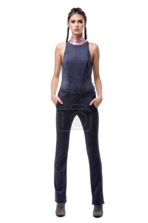 Photo for Beautiful girl standing in dark blue suede overalls and dreamily looking in camera on white background - Royalty Free Image