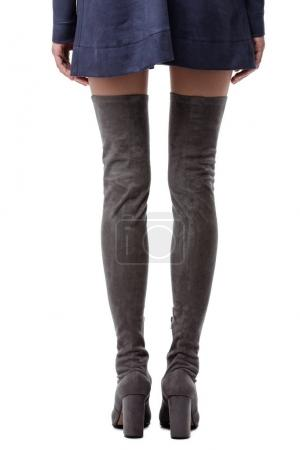 Close up photo of long woman legs in gray boots with heels