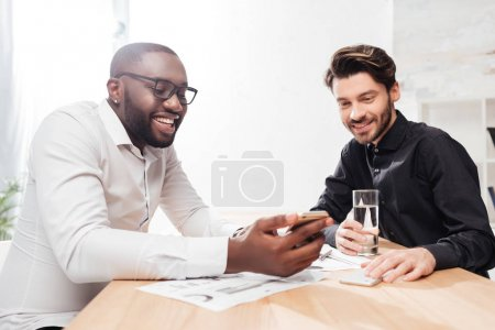 Portrait of two young joyful multinational businessmen sitting at the table and happily talking while working together in office isolated