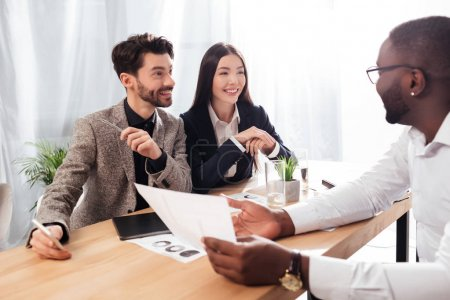 Portrait of young smiling multinational businessmen and businesswoman sitting at the table and discussing new project while working together in office