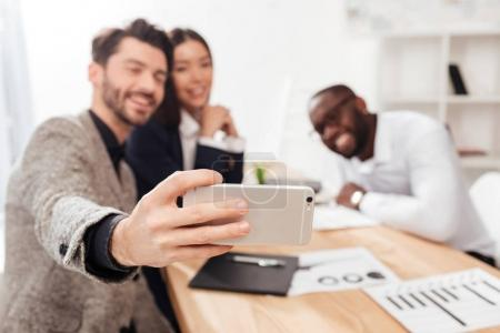 Close up photo of multinational businessmen and businesswoman sitting at the table and taking photos on frontal camera of cellphone while working together in office isolated