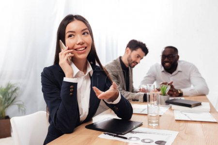 Portrait of beautiful asian businesswoman sitting in office and joyfully looking aside while talking on her cellphone with multinational business partners on background