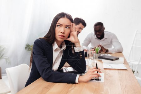 Portrait of young asian businesswoman sitting in office and looking aside with multinational business partners on background