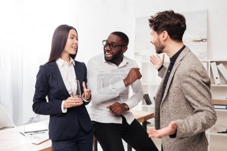 Portrait of smiling multinational businessmen and businesswoman standing near table and talking while working together in office isolated