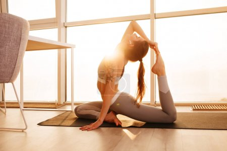 Portrait of young pretty lady in sporty top and leggings sitting and training yoga poses on yoga mat at home with big window on background