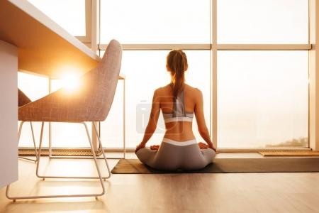 Portrait of young beautiful lady sitting in lotus pose on yoga mat and meditating near big windows at home isolated