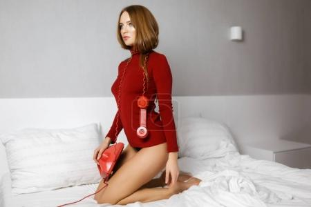 Photo for Portrait of young thoughtful woman in red turtleneck sitting in bed with red classic telephone and amazedly looking aside isolated - Royalty Free Image