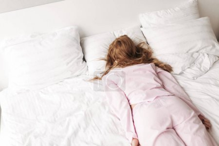 Portrait of young lady in pink pajamas lying in bed at home isolated