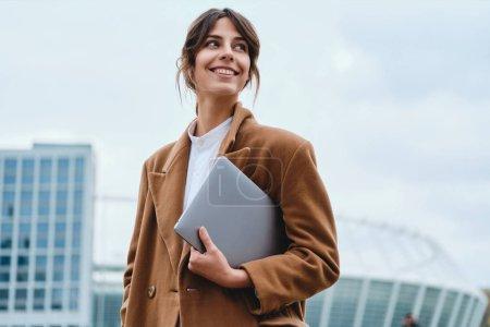 Foto de Joven mujer de negocios bastante sonriente en abrigo con portátil mirando felizmente en la calle de la ciudad - Imagen libre de derechos