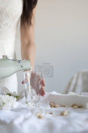 Photo pour Fille, verser le lait de noix de cajou Raw Vegan en verre - image libre de droit
