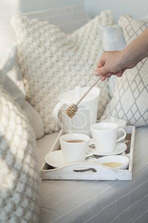 Photo pour Femme, verser le miel dans une tasse blanche avec thé à la menthe - image libre de droit
