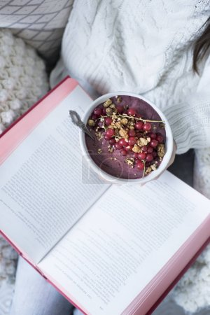 woman holding book and Acai Bowl