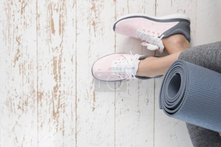 Photo pour Jeune femme en chaussures de sport avec tapis gris sur sol en bois minable - image libre de droit