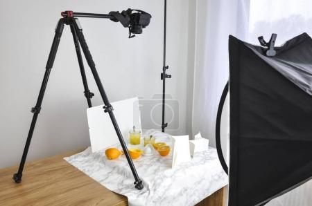 Photo for Photo camera on tripod above juice and oranges on table, food blog concept - Royalty Free Image