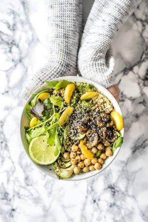 Photo for Woman holding vegan buddha bowl with avocado, mushrooms, radish, sweet potato, green leaves, lemon and quinoa - Royalty Free Image