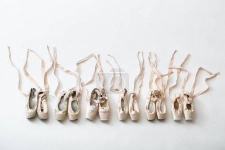 Photo pour Plusieurs paires de chaussures de ballet en couples se tiennent dans une rangée. Chaussons de pointe dans un état différent de nouveau à minable très ancien. Bandes sont disposées avec précision dans des directions différentes. Studio de tournage, horizontale - image libre de droit
