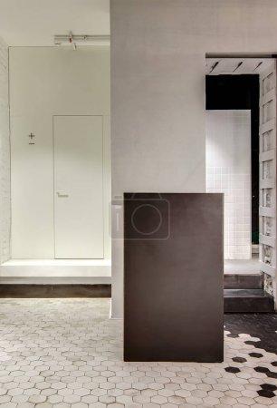 Photo pour Couloir lumineux avec des murs blancs à l'intérieur dans un style loft avec la tuile noire et blanche sur le sol. Il y a une porte blanche, un stand sombre et une entrée avec deux escaliers menant à la pièce voisine - image libre de droit