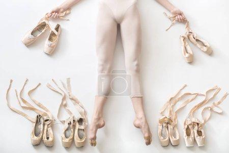 Photo pour Belle ballerine se trouve avec les jambes étirées sur le sol blanc en studio. Elle porte une usure légère danse et détient des rubans de chaussures dans les mains. Sur les côtés des jambes il y a des chaussures de ballet. - image libre de droit