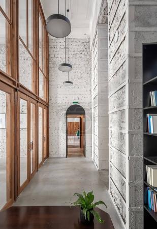 Photo pour Intérieur dans un style loft dans le café avec des murs légers et minables plancher gris. Il y a une table en bois avec une plante, des étagères noires avec des livres, une grande cloison en verre avec des portes, des lampes suspendues . - image libre de droit